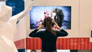 A woman watching a video screen at the Canadian Olympic House experience